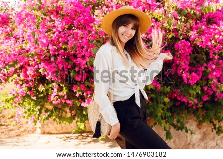 Playful  woman standing over  flowers background. Wearing straw hat and casual outfit.  #1476903182