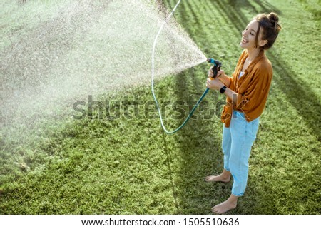 Playful woman watering green lawn, sprinkling water on the grass during a sunny morning on the backyard. Lawn care concept #1505510636