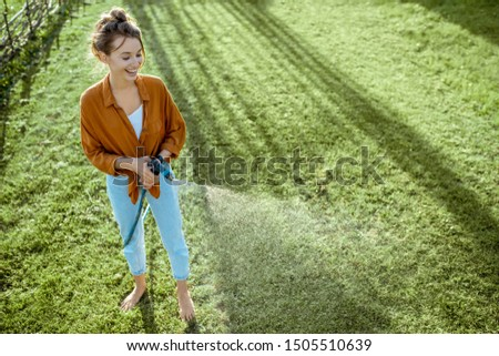 Playful woman watering green lawn, sprinkling water on the grass during a sunny morning on the backyard. Lawn care concept #1505510639