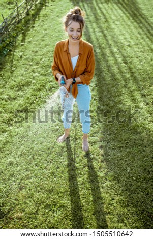 Playful woman watering green lawn, sprinkling water on the grass during a sunny morning on the backyard. Lawn care concept #1505510642