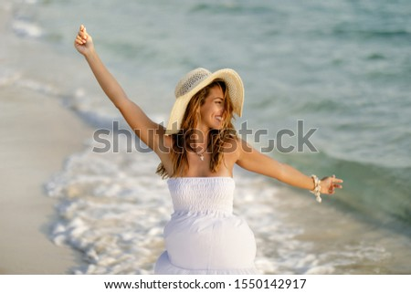 Playful woman wit arms outstretched having fun while dancing at the beach.  #1550142917