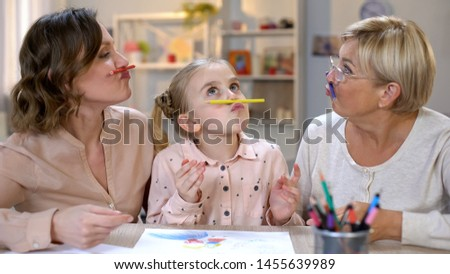 Playful woman with daughter and granddaughter holding pencils like mustache, fun #1455639989