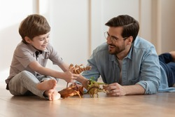 Playful young Caucasian father lying on floor play toy figure with small 7s boy child. Happy dad relax at home have fun engaged in funny game activity with little son on weekend together.