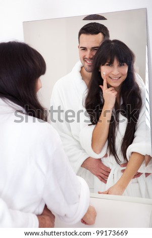 Playful young couple applying cream in the bathroom - stock photo