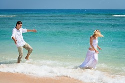 Playful young couple have a fun in blue sea water on the tropical beach
