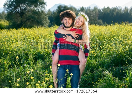 Playful young couple in a yellow rapeseed field smiling happily at the camera as the young man gives his beautiful young girlfriend a piggy back ride