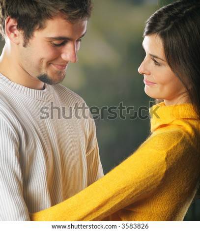 Playful young happy smiling attractive couple embracing, outdoors