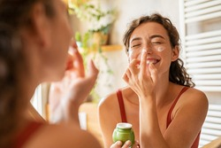 Playful young woman applying cream on nose. Girl holding green lotion jar applying moisturizer on nose. Beautiful woman taking care of skin by applying moisturizer every day in the morning.