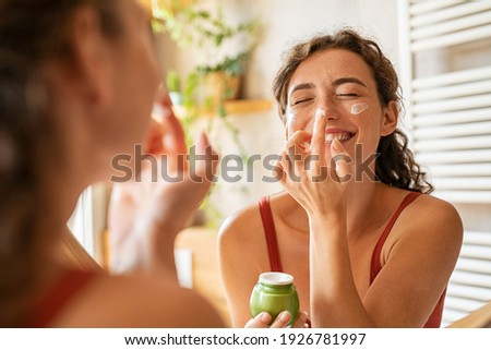 Playful young woman applying cream on nose. Girl holding green lotion jar applying moisturizer on nose. Beautiful woman taking care of skin by applying moisturizer every day in the morning. Foto d'archivio ©