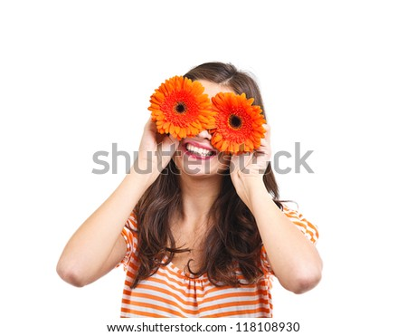 Playful young woman covering her eyes with flowers