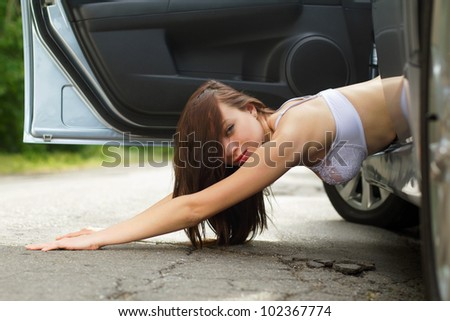 Playful young woman lying on the road