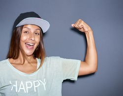 Playful young woman pumping her muscles flexing her arm to show off her biceps with a laughing smile, over grey