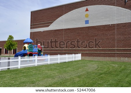 Playground and a white fence by a modern red brick school building.  There is a bright green lawn by the fence.