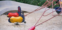Playground. Children playground with soft focus on the yellow empty swing seat.