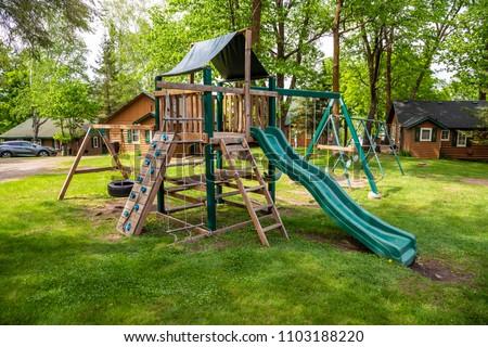 Playground play set swing slide rock climb wall tire monkey bars summer grass green
