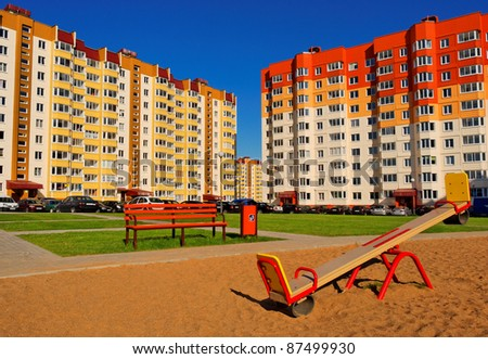 playground with seesaw and bench between high apartment houses