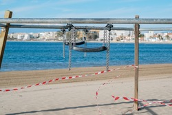 Playgrounds closed for pandemic Covid-19 on blue sea background. Caution tape wrapped around outdoor recreation and entertainment areas to prevent spread of virus. Empty playground in Europe. Spain.