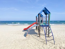 Playhouse for kids on the sand near the sea. Playground area on the beach, sunny day, nobody. Concept of recreation, kids activity, putdoor ammusement.