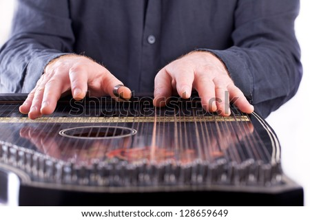 playing a traditional musical instrument, It belongs to the zither family of string instruments