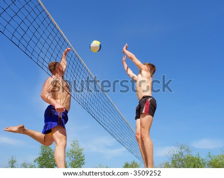 Playing beach volleyball - man and teenager compete for ball above net. Shot near Dnieper river, Ukraine.