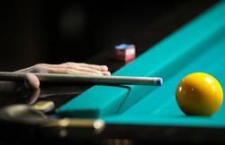 Playing billiard. Player's arm gets ready to stroke a ball with a cue