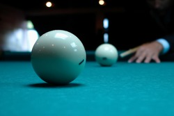 Playing billiards. Billiard balls and cue on a green pool table. Billiard sports concept. Pool billiard game. Russian billiards, pyramid of billiards, cue sport