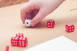 Playing board games, dices in child hand