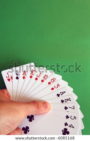 playing bridge - one hand (Q spade, J heart, A,K,J,10,8,3 diamonds, A,K,7,5,4 clubs)  background green, selective focus