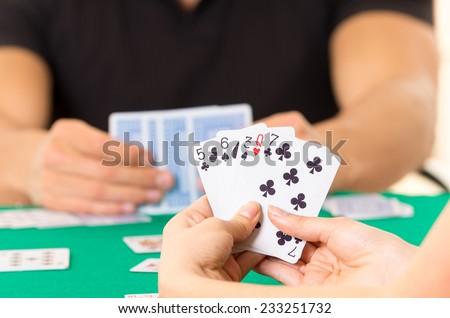 Playing cards closeup of hands holding deck cuarenta traditional Ecuadorian game