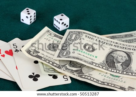 Playing cards dice and bills of American currency on a green gaming table
