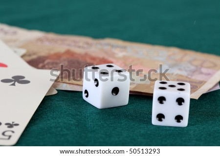 Playing cards dice and two bills of Moroccan currency on a green gaming table