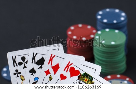 Playing cards of kings against the background of poker chips on a black background