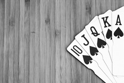 Playing cards royal flush close up, isolated on wooden table. Casino concept, risk, chance, good luck or gambling.