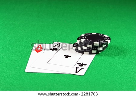 Playing cards showing a pair of aces with poker chips next to them - stock photo