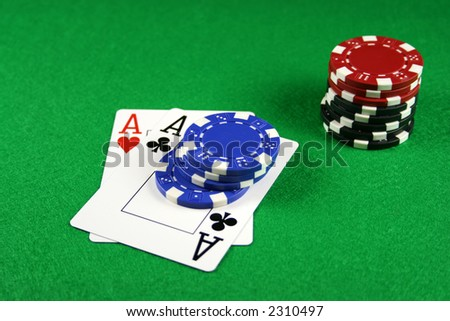 Playing cards showing a pair of aces with poker chips next to them