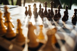 Playing chess on a chessboard at sunset. Tactics and strategy. Black and white figures.