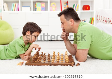 Playing chess with dad - young boy and his father at home