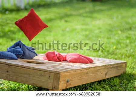playing cornhole in backyard throwing bag in air