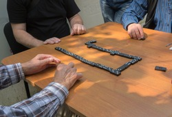 Playing dominoes on a wooden table background . Man's hand on a domino. Domino concept. Several men play dominoes in the backyard.