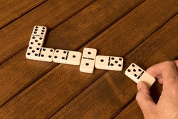 Playing dominoes on a wooden table . Man's hand with a Domino.