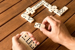 Playing dominoes on a wooden table. Man's hand with dominoes.