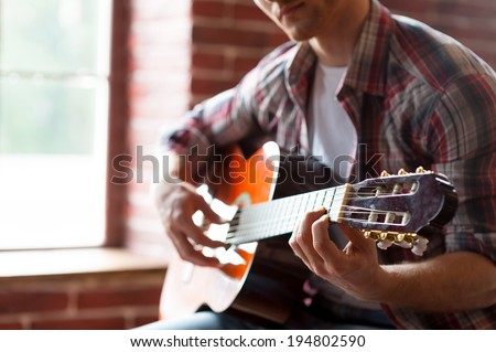 Playing guitar. Close-up of man playing acoustic guitar while sitting in front of the window
