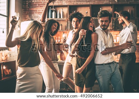 Playing hard. Cheerful young people dancing and drinking while enjoying home party on the kitchen