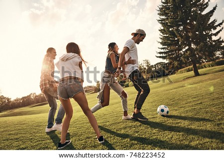 Playing hard. Full length of young people in casual wear running while playing soccer outdoors