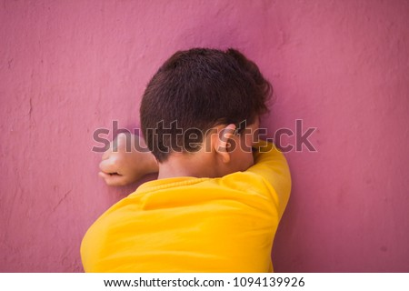 playing hide and seek. boy closed eyes his hands standing at wall