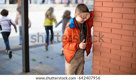 playing hide and seek. european boy closed eyes his hands standing at brick wall