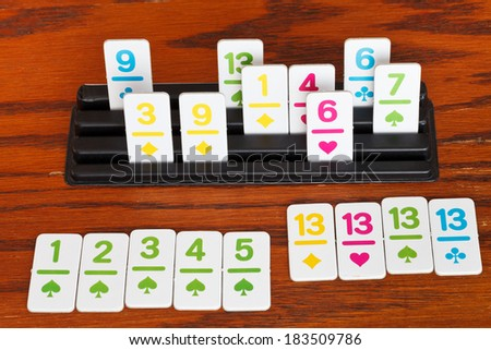 playing in rummy card game on wooden table - run and group of cards