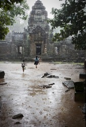 playing in the rain at angkor in cambodia