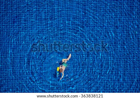 Playing in water. Top view of little boy swimming in the pool.