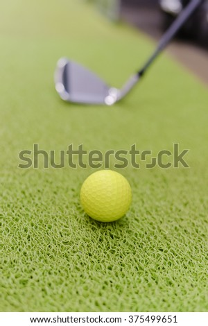 Playing indoors. Golf club and ball on green carpet grass background texture #375499651
